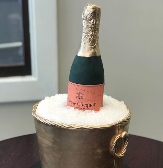 A wedding cake in the shape of a bottle of champagne in a bucket of ice